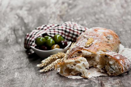 Homemade  mixed olive ciabatta on rustic wooden table  Banque d'images