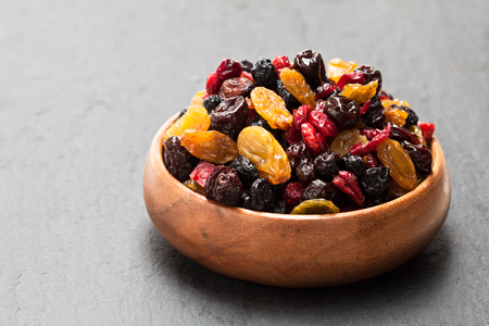 Dried  berries and fruits in wooden bowl on black stone background