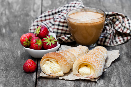 Puff  pastry horns with cup of cappuccino and strawberry on wooden table