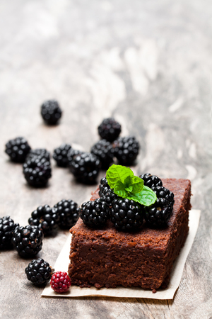 Homemade  chocolate brownie with berries on wooden table
