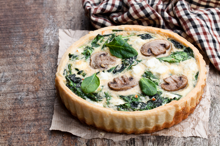 Traditional  french quiche pie with spinach and mushroom on wooden table Stock Photo