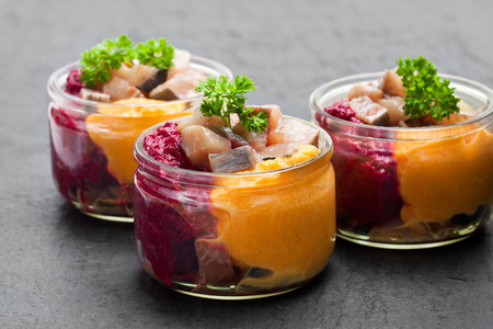 Herring  salad with colorful vegetables in a small glass jars on black stone background