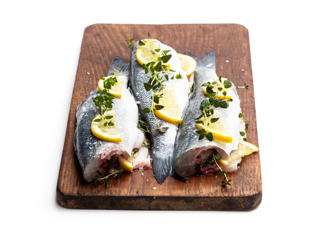 Fresh  whole sea bass fish with lemon and herbs isolated on a white