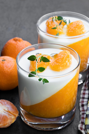 Panna cotta with mandarine jelly in clear glass on black stone background