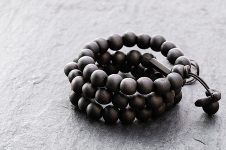 Beads  rosary on black stone background 스톡 콘텐츠