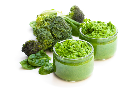 Green puree in glass jars isolated on white