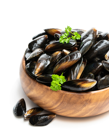 Raw mussels in wooden bowl isolated on white