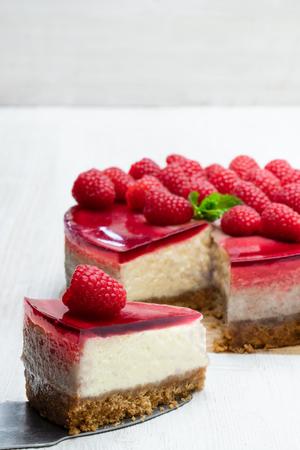 Cheesecake fatta in casa con gelatina di lamponi sul tavolo di legno bianco