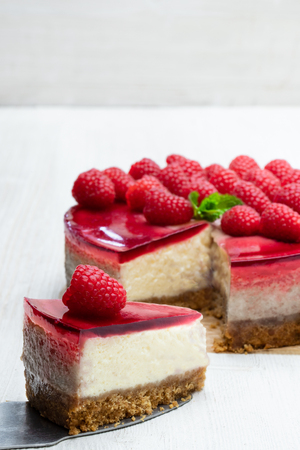 Homemade cheesecake with raspberry jelly on white wooden table