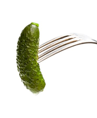 Pickled  cucumber sticking on a fork isolated on white