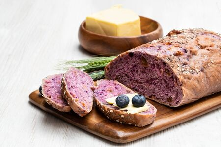 Blueberry  and chia seed bloomer with butter on white wooden table