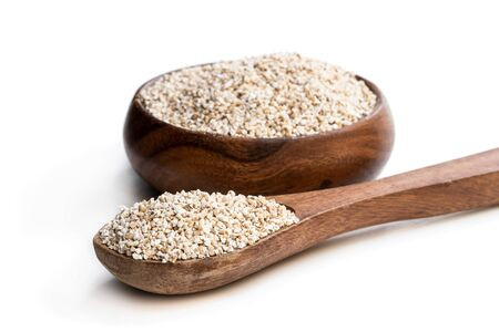 Barley  groats in wooden bowl isolated on white