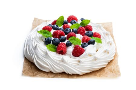 Pavlova  meringue nest with berries and mint leaves isolated on white