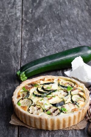 Homemade  courgette and feta quiche on white wooden table