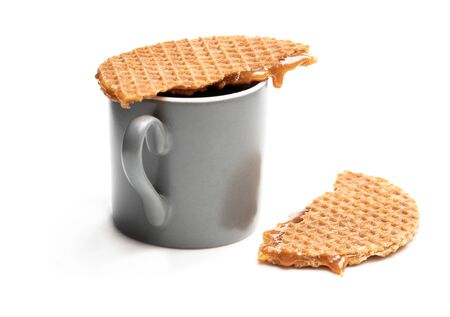 Melted  Dutch caramel waffle on cup of coffee isolated on white Imagens