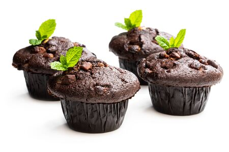 Four  chocolate muffins isolated on white decorated with mint leaves Imagens