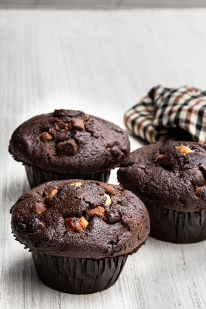 Three  chocolate muffins on the rustic table with cloth napkin