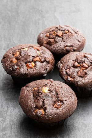 Four  chocolate muffins on the rustic grey table