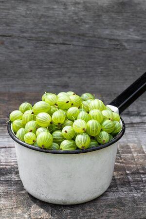 Fresh  ripe green gooseberry on wooden background  Imagens