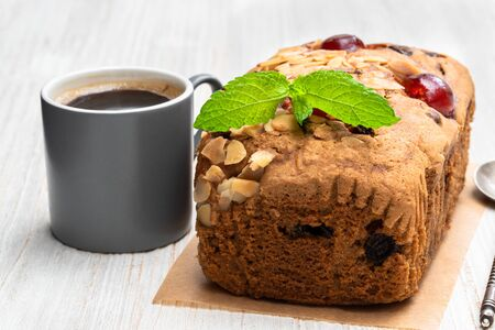 Mixed  fruit loaf cake with cup of coffee on wooden table