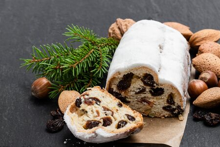 Traditional Christmas stollen fruit cake on black stone table