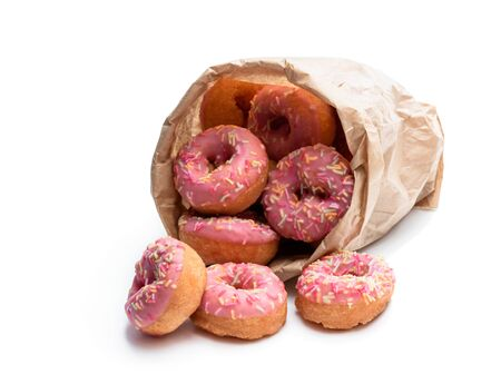 Mini pink glazed doughnuts in paper bag isolated on white