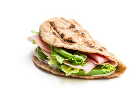 Folded  wholemeal flatbread with ham and vegetables isolated on white