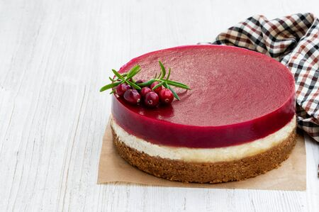 Delicious  layered cranberry cheese cake on white wooden table