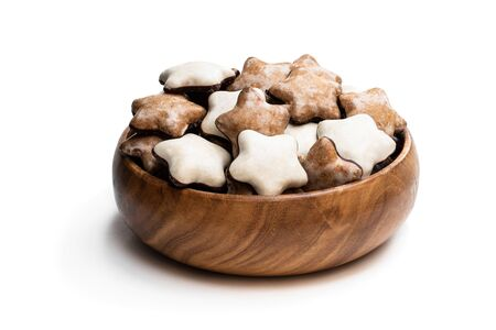 Sugar and chocolate glazed seasonal spiced cookies in wooden bowl isolated on white