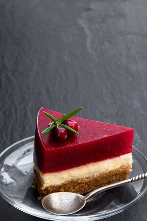 Delicious  layered cranberry cheese cake on black stone background  Stock Photo