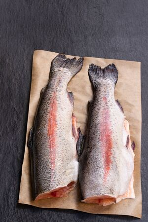 Fresh  raw trout fish with head removed on black stone