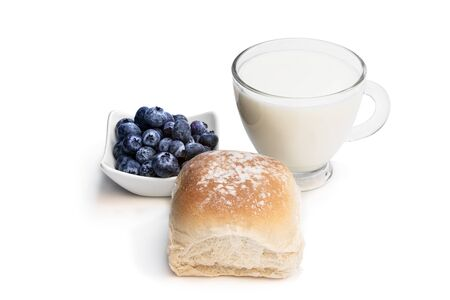 Freshly baked wheat bun with blueberry and glass of milk isolated on white
