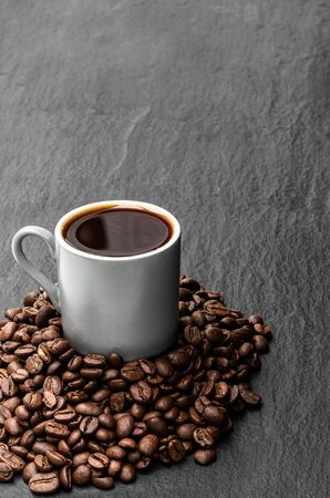 Schwarzer Kaffee in kleiner Tasse mit Bohnen auf schwarzem Steinhintergrund Standard-Bild