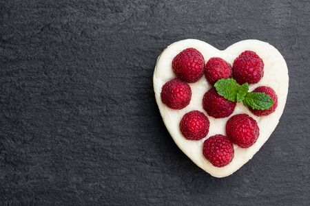 Heart  shaped cheesecake with raspberry on black stone background. Top view