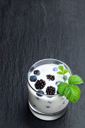 Drinking  yogurt with fresh berries in a glass on black stone background