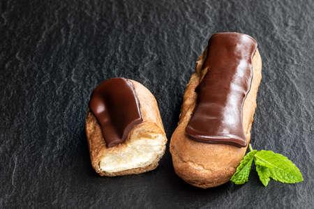 Chocolate eclairs on black stone background