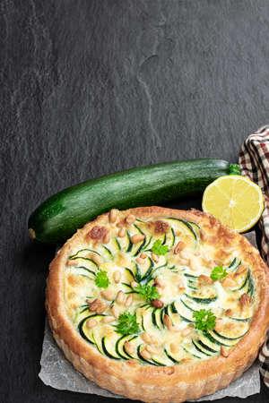 Vegetarian pizza with zucchini and pine nuts on black stone background Zdjęcie Seryjne