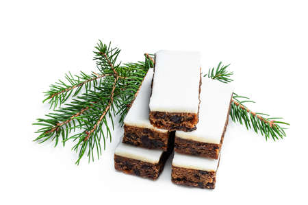 Fruit cake slices topped with marzipan isolated on white