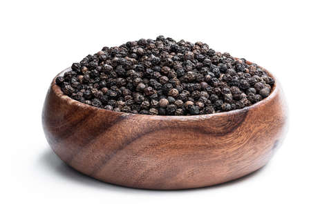 Black pepper corn in wooden bowl isolated on white