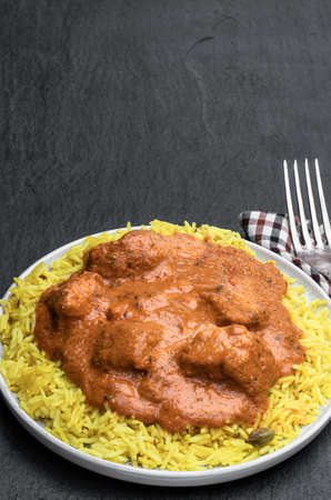 Chicken Tikka Masala with pilau rice on black stone background