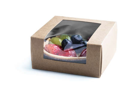 Fresh fruit tart with berries in small card box isolated on white