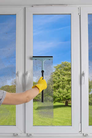 Cleaning modern PVC windows with a hand-held squeegee concept Banque d'images