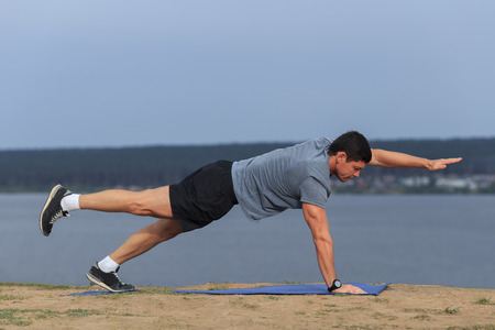 young man doing yoga outside in natural environment