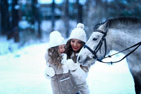 pony girl: little girl and mom feeding little horse pony winter Stock Photo