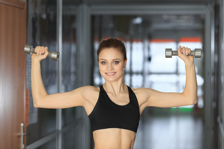 photo of athletic young girl standing with dumbbells