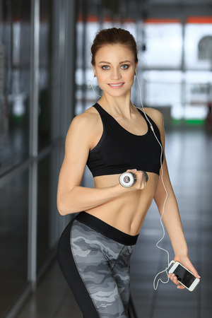 Beautiful fitness woman standing with dumbbell and the telephone