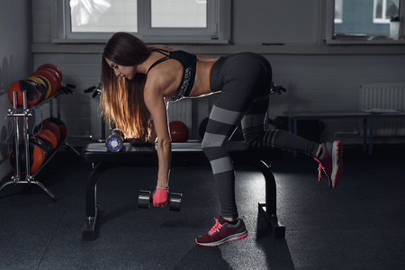 musculation: fitness brunette girl with trained body are training back with dumbbell at gym