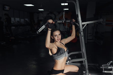 lat: Beautiful young woman doing exercise for back on lat machine