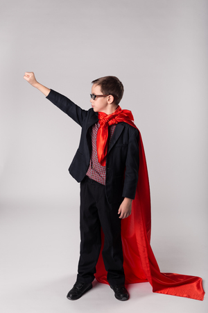 Young playful business kid hand up in  super hero cape and suit Stock Photo