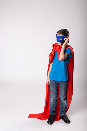 Super hero kid using mobile phone.  kid in red cape and blue mask